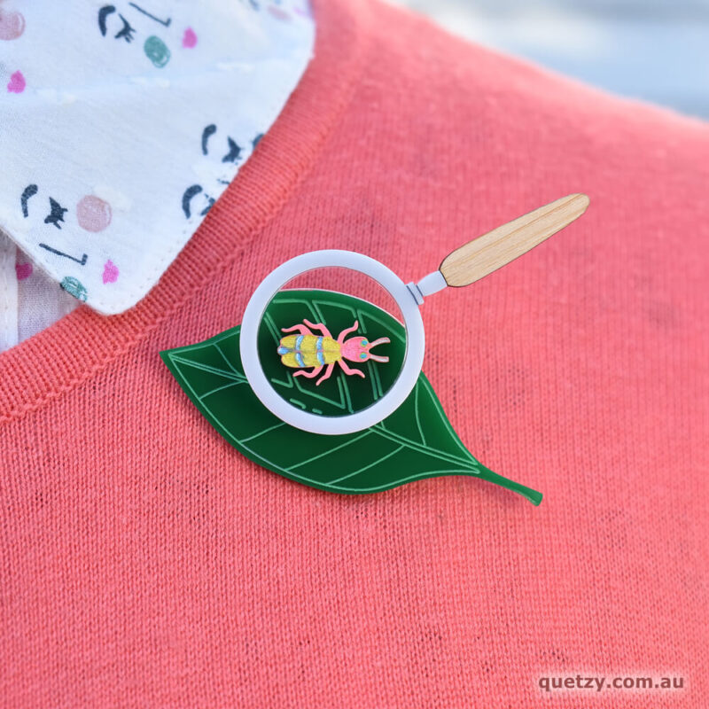 Magnification Bug acrylic brooch. Designed, laser cut and handmade by Quetzy.