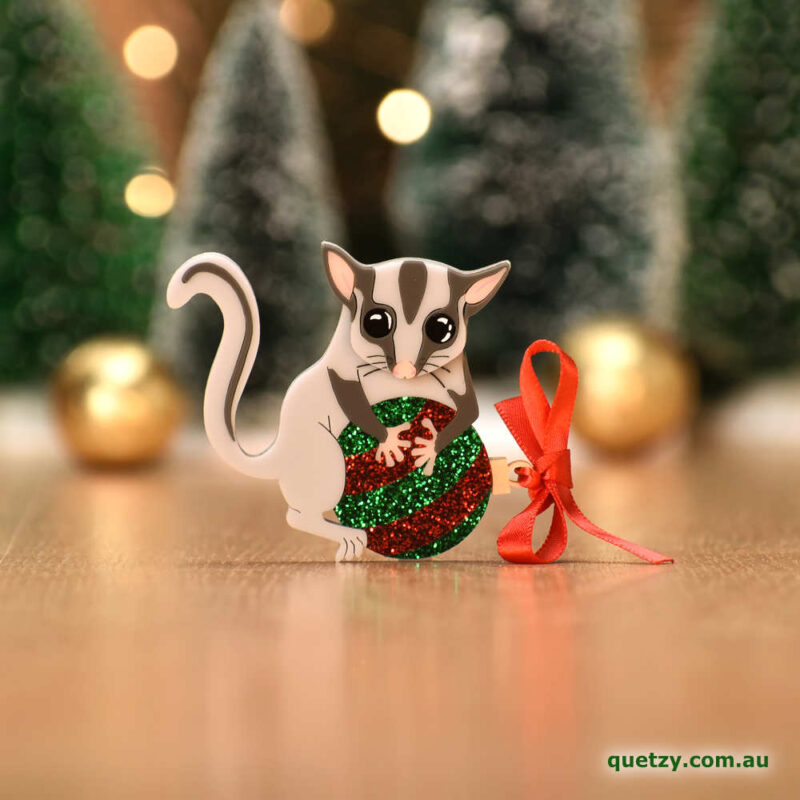 Lottie the Leadbeater's Possum with glitter red and green bauble. A Christmas themed acrylic brooch, designed and handmade by Quetzy.