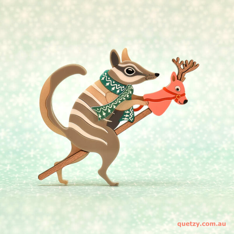 Nimble Numbat riding a toy stick reindeer. A Christmas themed acrylic brooch, designed and handmade by Quetzy.